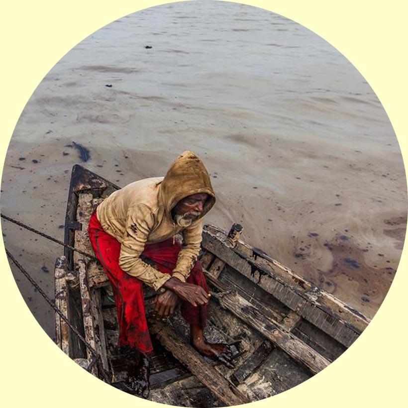 fisherman-at-bangladesh-scourging-foul-oil-from-river